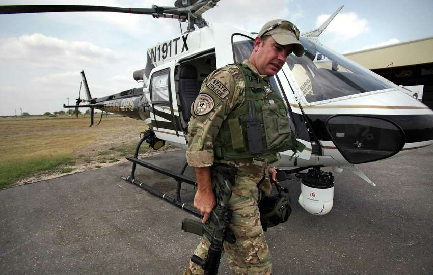 DPS State Police Capt. Stacy Holland carries an M-4 rifle after a flight patroling the Rio Grande River by high tech helicopters based in Edinburg, TX. Thursday, May 3, 2012.