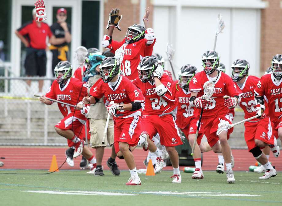 The Fairfield Prep lacrosse team runs out on the field to celebrate their 8-6 victory over Ridgefield in the Class L Final lacrosse championship at Brien McMahon High School on Saturday June 9, 2012. Photo: J. Gregory Raymond / Connecticut Post Freelance