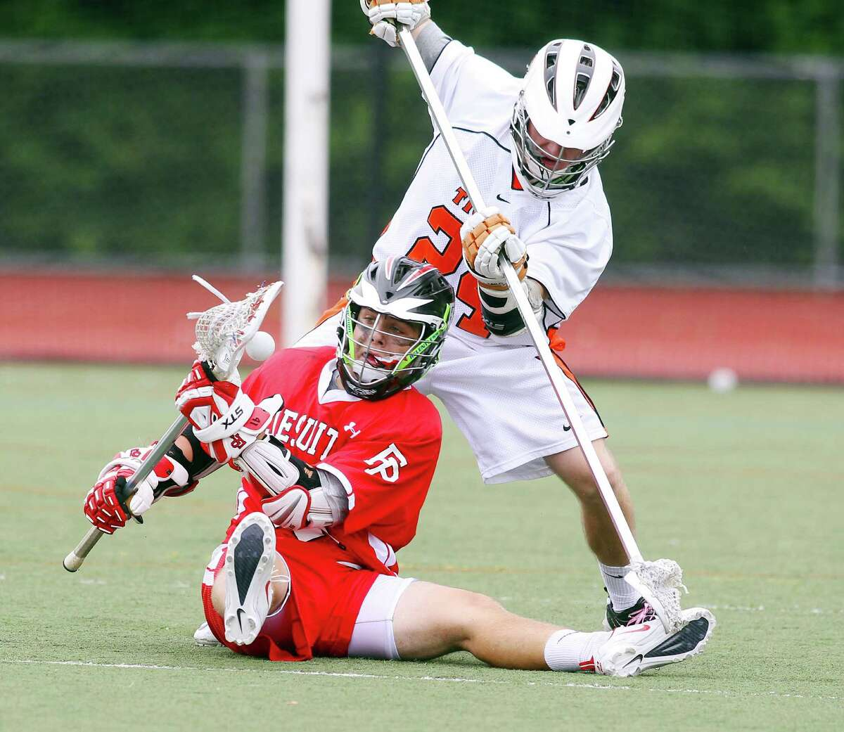 Kevin Brown of Fairfield Prep controls the ball despite the defensive efforts of Ridgefields's Brendan Bossidy during the Class L Final lacrosse championship at Brien McMahon High School on Saturday June 9, 2012. Fairfield Prep beat Ridgefield, 8-6.