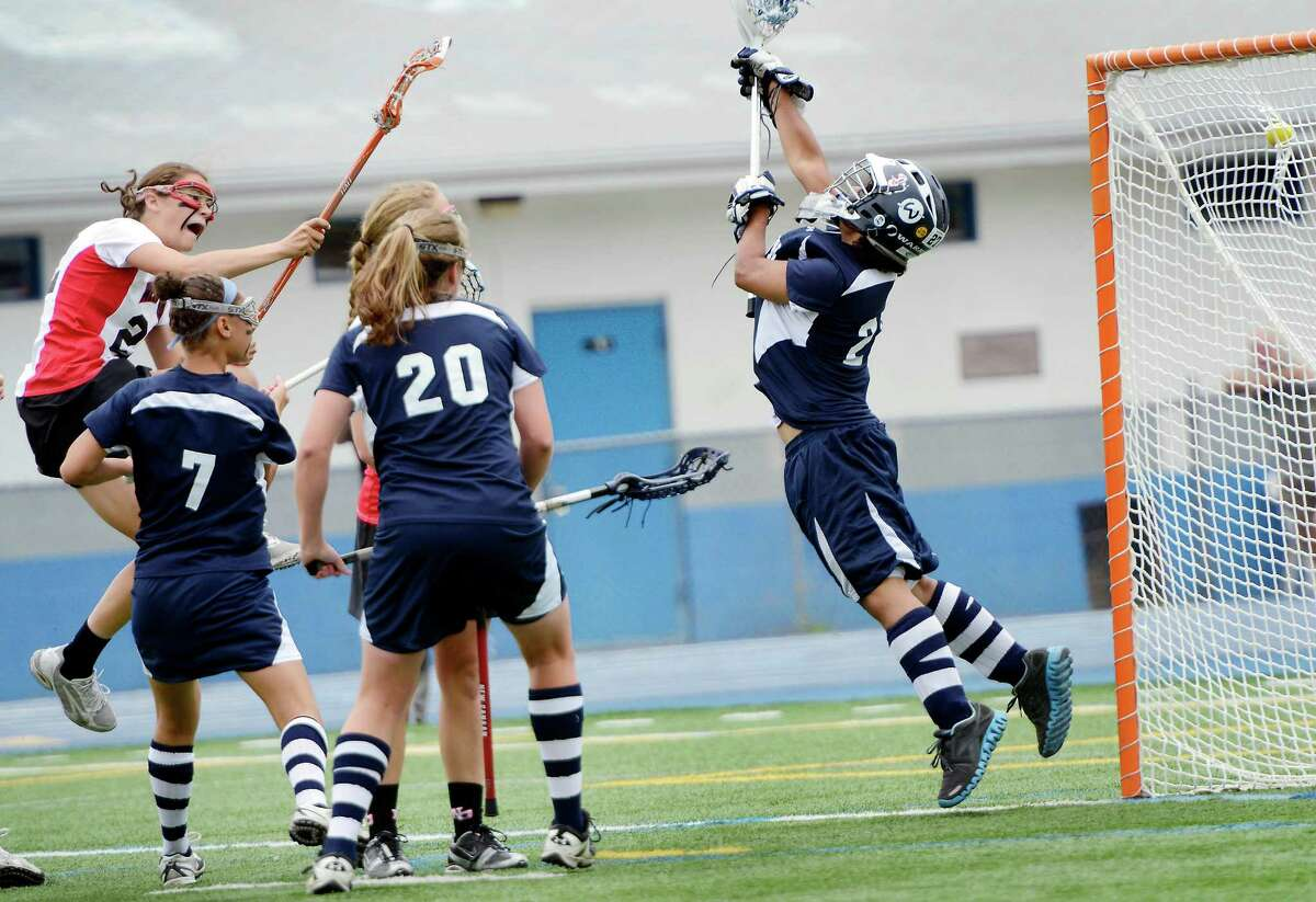 New Canaan High School's Olivia Hompe scores her first goal of the game against Wilton High School in the CIAC Class M girls lacrosse championship held at Bunnell High School, Stratford, CT on Saturday June 9th, 2012. Wilton goalie Vanesa Pagano could not make the save.