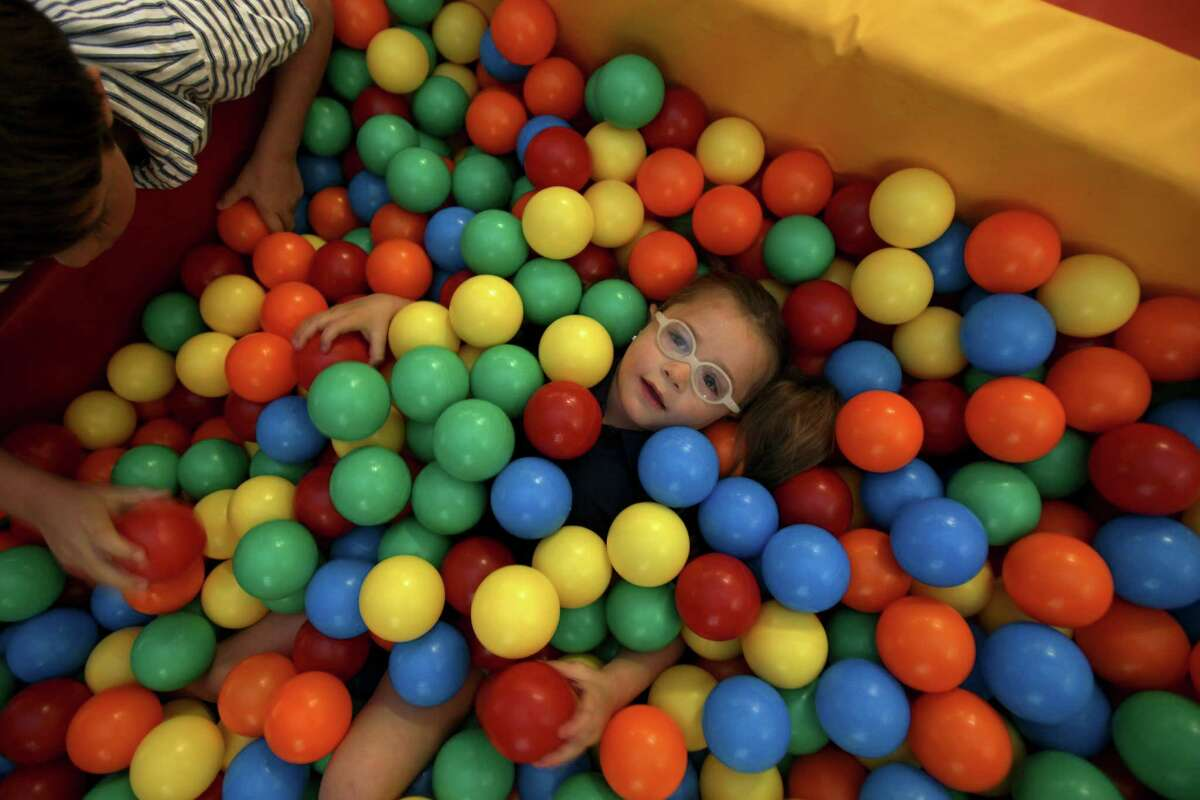 """Ava Lopez, 4, """"swims"""" in a ball pit during her therapy session Thursday June 7, 2012 at Pediatric Therapy Specialists. Ava has endured countless therapy since the accident that left her in a coma in 2009 after a drunk driver hit her, her sister and mother while doing yardwork outside. Ava was 18 months at the time and had to relearn almost everything from crawling, to swallowing liquids."""