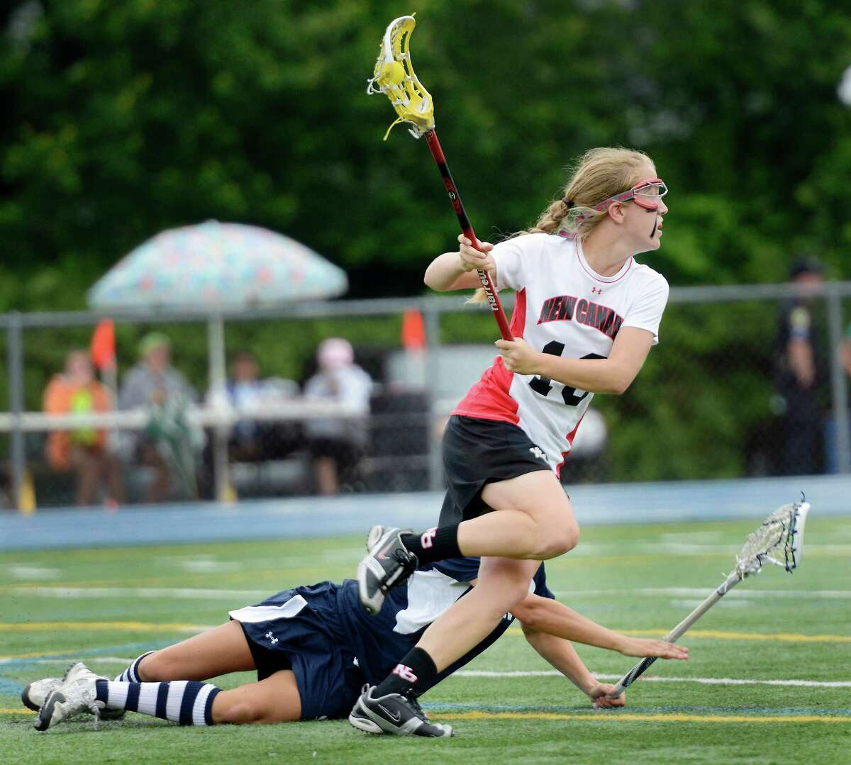 New Canaan High School's Sarah Mannelly gets by Wilton High School's Samantha Blicht in the CIAC Class M girls lacrosse championship held at Bunnell High School, Stratford, CT on Saturday June 9th, 2012.