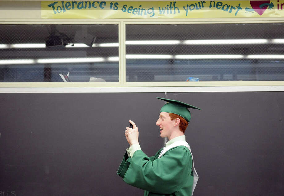 Michael Murphy takes a photo of friends before Saturday's graduation ceremony at Trinity Catholic High School in Stamford on June 9, 2012. Photo: Lindsay Niegelberg / Stamford Advocate