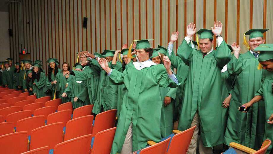 Students do the wave as they wait in the auditorium before Saturday's graduation ceremony at Trinity Catholic High School in Stamford on June 9, 2012. Photo: Lindsay Niegelberg / Stamford Advocate