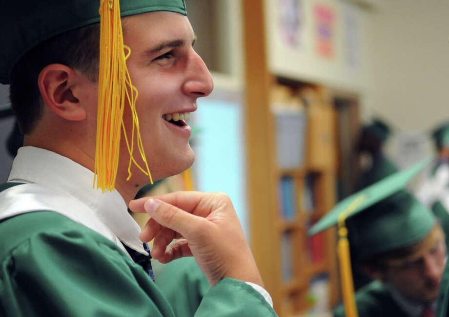 John McMullen laughs with friends before Saturday's graduation ceremony at Trinity Catholic High School in Stamford on June 9, 2012. Photo: Lindsay Niegelberg / Stamford Advocate