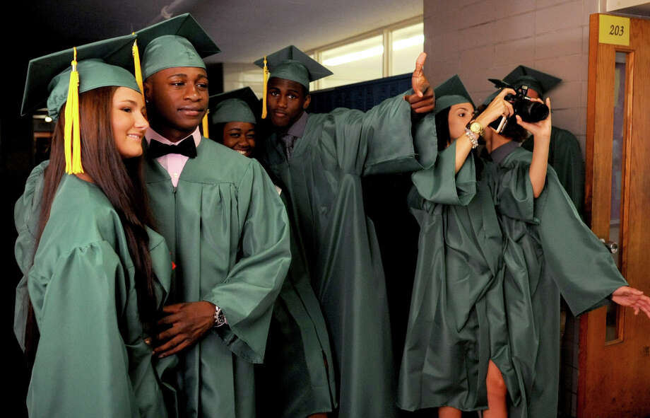 Seniors pose for photos before Saturday's graduation ceremony at Trinity Catholic High School in Stamford on June 9, 2012. Photo: Lindsay Niegelberg / Stamford Advocate
