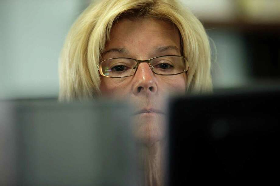 Library clerk Jane Stahl works on a computer at a San Diego Public Library Friday, June 8, 2012, in San Diego. Stahl has worked for the city as a librarian for seven years. Voters in San Diego and San Jose overwhelmingly approved ballot measures last week to roll back municipal retirement benefits - and not just for future hires but for current employees. (AP Photo/Gregory Bull) Photo: Gregory Bull / AP