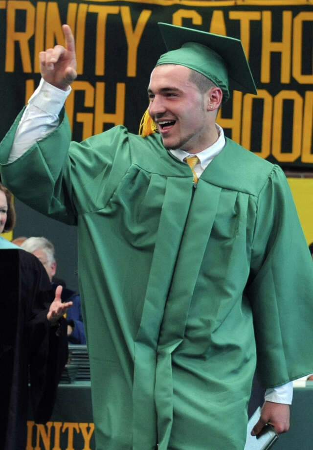 Patrick King points into the crowd after getting his diploma during Saturday's graduation ceremony at Trinity Catholic High School in Stamford on June 9, 2012. Photo: Lindsay Niegelberg / Stamford Advocate