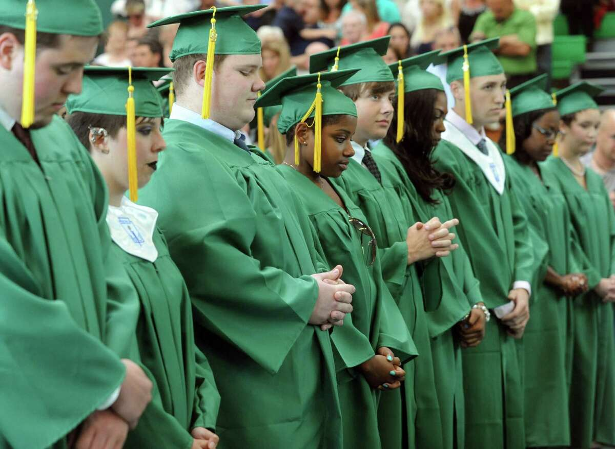 Students bow their heads during the invocation during Saturday's graduation ceremony at Trinity Catholic High School in Stamford on June 9, 2012.