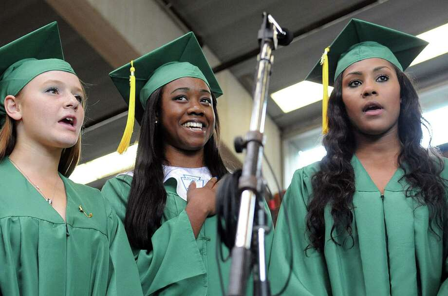 From left, Victoria Gargiulo, Jessica Ankle and Maya Ferguson sing the Star Spangled Banner during Saturday's graduation ceremony at Trinity Catholic High School in Stamford on June 9, 2012. Photo: Lindsay Niegelberg / Stamford Advocate