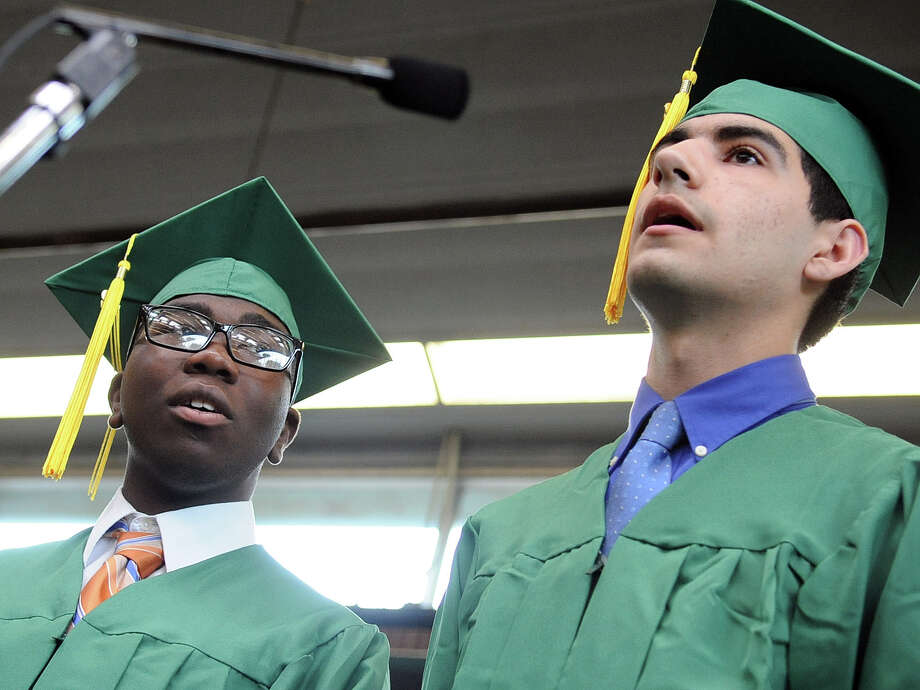 Joel Fleurantin, left, and Colby Rich, right, sing the Star Spangled Banner during Saturday's graduation ceremony at Trinity Catholic High School in Stamford on June 9, 2012. Photo: Lindsay Niegelberg / Stamford Advocate