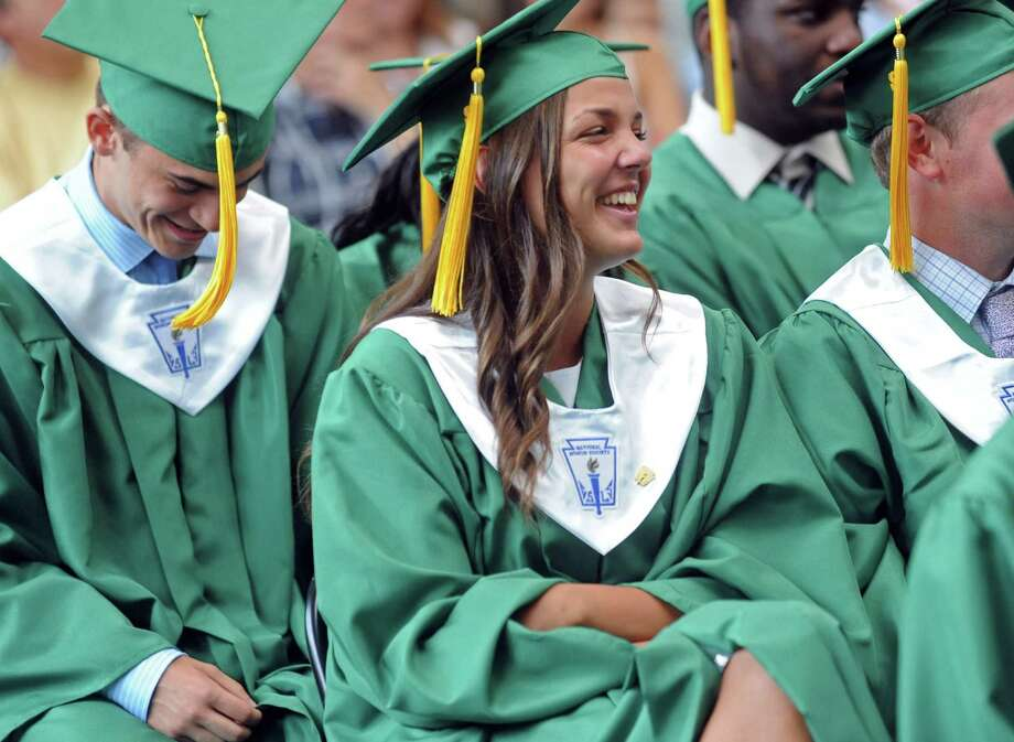 Matthew Sheridan, left, and Brett-lyn Robustelli, right, laugh with classmates during salutatorian Kevin Epp's speech during Saturday's graduation ceremony at Trinity Catholic High School in Stamford on June 9, 2012. Photo: Lindsay Niegelberg / Stamford Advocate