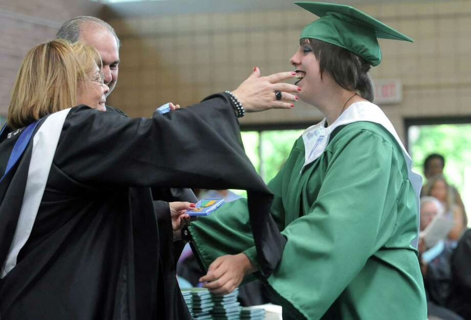 Danielle Brusco gets a hug as she is presented with the Art Award during Saturday's graduation ceremony at Trinity Catholic High School in Stamford on June 9, 2012. Photo: Lindsay Niegelberg / Stamford Advocate
