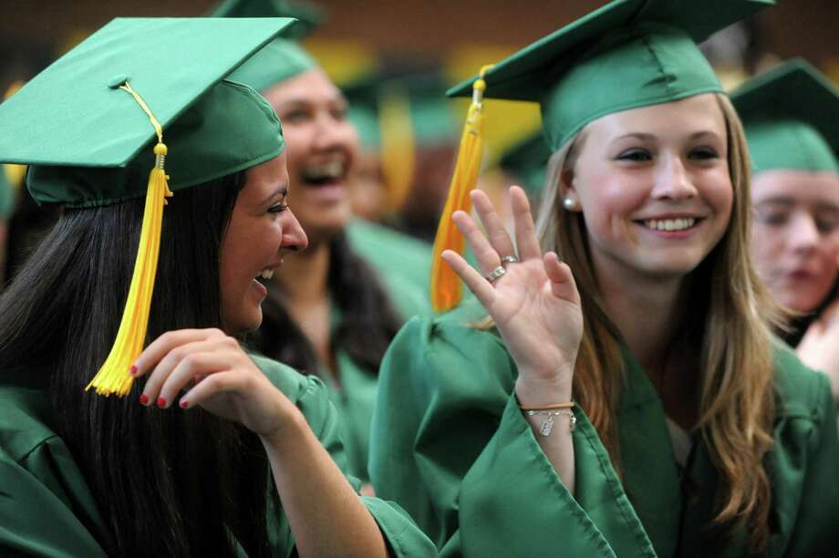 A classmate waves off Jessica Lofaro, left, in an effort to keep Jessica's tears from being contagious, during Saturday's graduation ceremony at Trinity Catholic High School in Stamford on June 9, 2012. Photo: Lindsay Niegelberg / Stamford Advocate