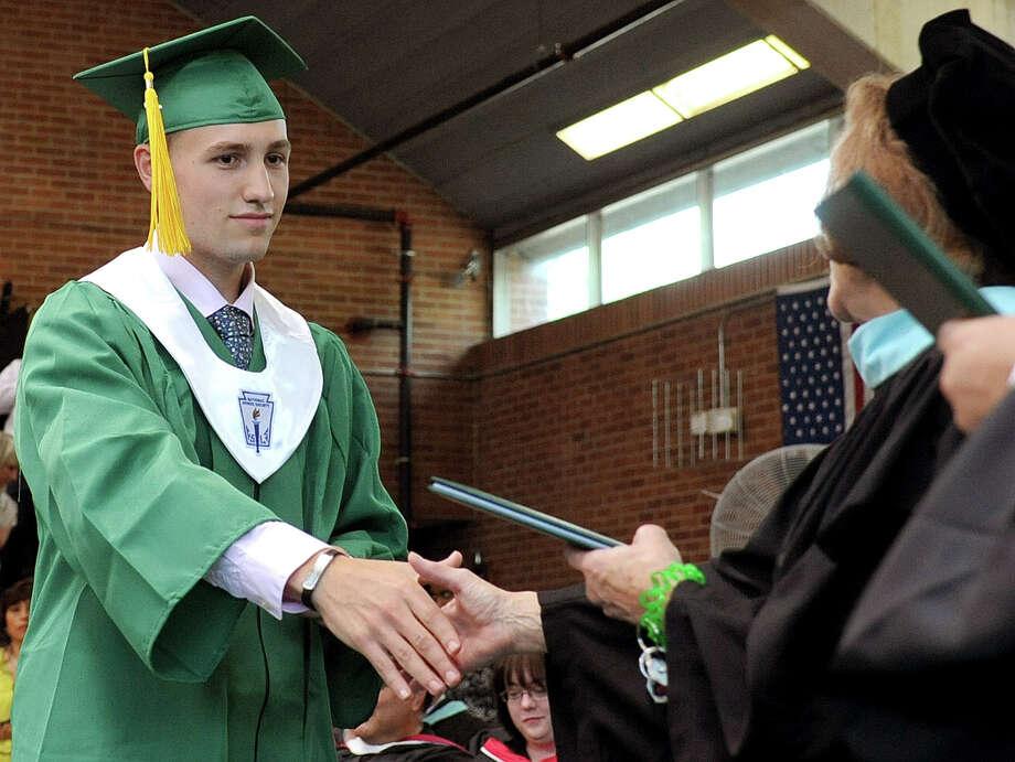Sean Baranowski gets his diploma during Saturday's graduation ceremony at Trinity Catholic High School in Stamford on June 9, 2012. Photo: Lindsay Niegelberg / Stamford Advocate