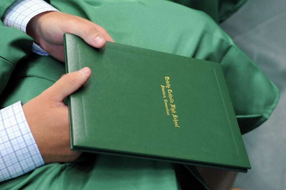 A student holds his diploma during Saturday's graduation ceremony at Trinity Catholic High School in Stamford on June 9, 2012. Photo: Lindsay Niegelberg / Stamford Advocate