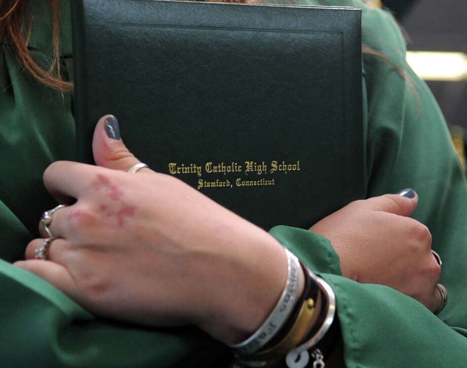 A student holds her diploma during Saturday's graduation ceremony at Trinity Catholic High School in Stamford on June 9, 2012. Photo: Lindsay Niegelberg / Stamford Advocate