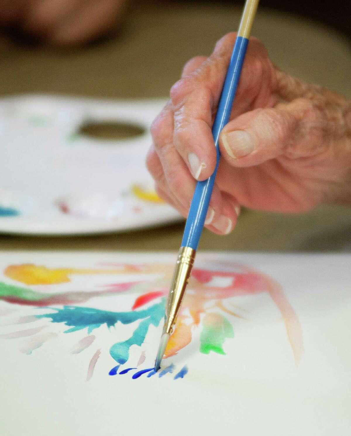 Memory art class participant Nettie Cook paints with watercolors, Monday, June 4, 2012, at Franklin Park in San Antonio.