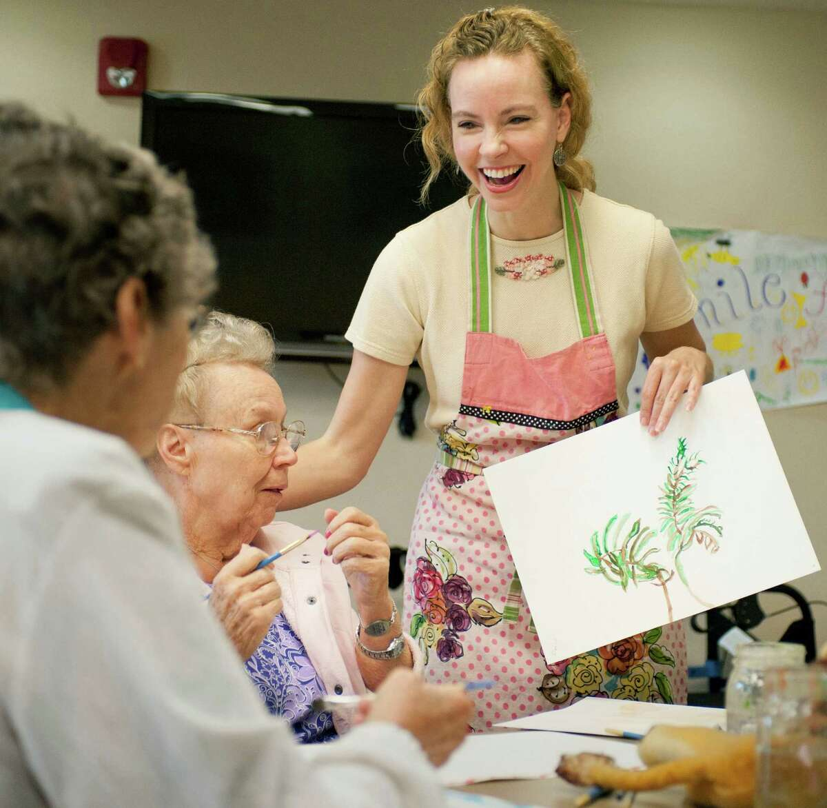 Memory art class teacher Gina Reese, right, shows a watercolor painting to participants Margaret Hockey, left, and Doris Maynard, Monday, June 4, 2012, at Franklin Park in San Antonio. (Darren Abate/Express-News)