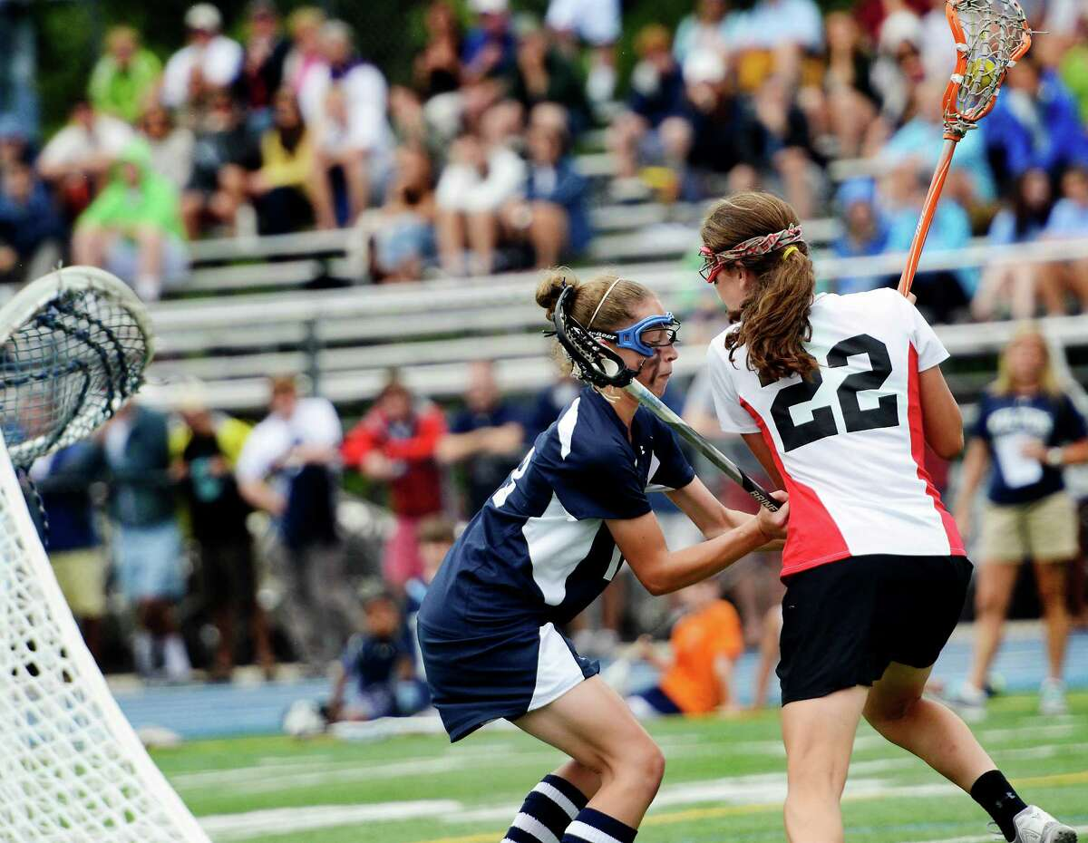 Wilton High School's Makenna Pearsall tries to keep New Canaan High School's Olivia Hompe from getting out in front of Wilton's goal during the CIAC Class M girls lacrosse championship held at Bunnell High School, Stratford, CT on Saturday June 9th, 2012.