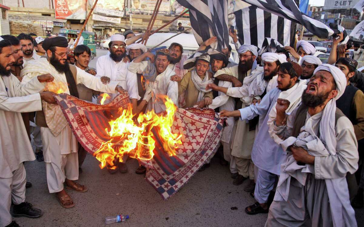 FILE - In this Friday, June 1, 2012 file photo, supporters of Pakistan Defense Council, a coalition of Islamic parties, burn a representation of a US flag at rally to condemn the reopening of the NATO supply line to neighboring Afghanistan, in Quetta, Pakistan. The U.S. and Pakistan are starting to look more like enemies than friends, threatening the U.S. fight against Taliban and al-Qaida militants based in the country and efforts to stabilize neighboring Afghanistan before American troops withdraw. The latest irritant is Pakistan's refusal to end its six-month blockade of NATO troop supplies meant for Afghanistan.
