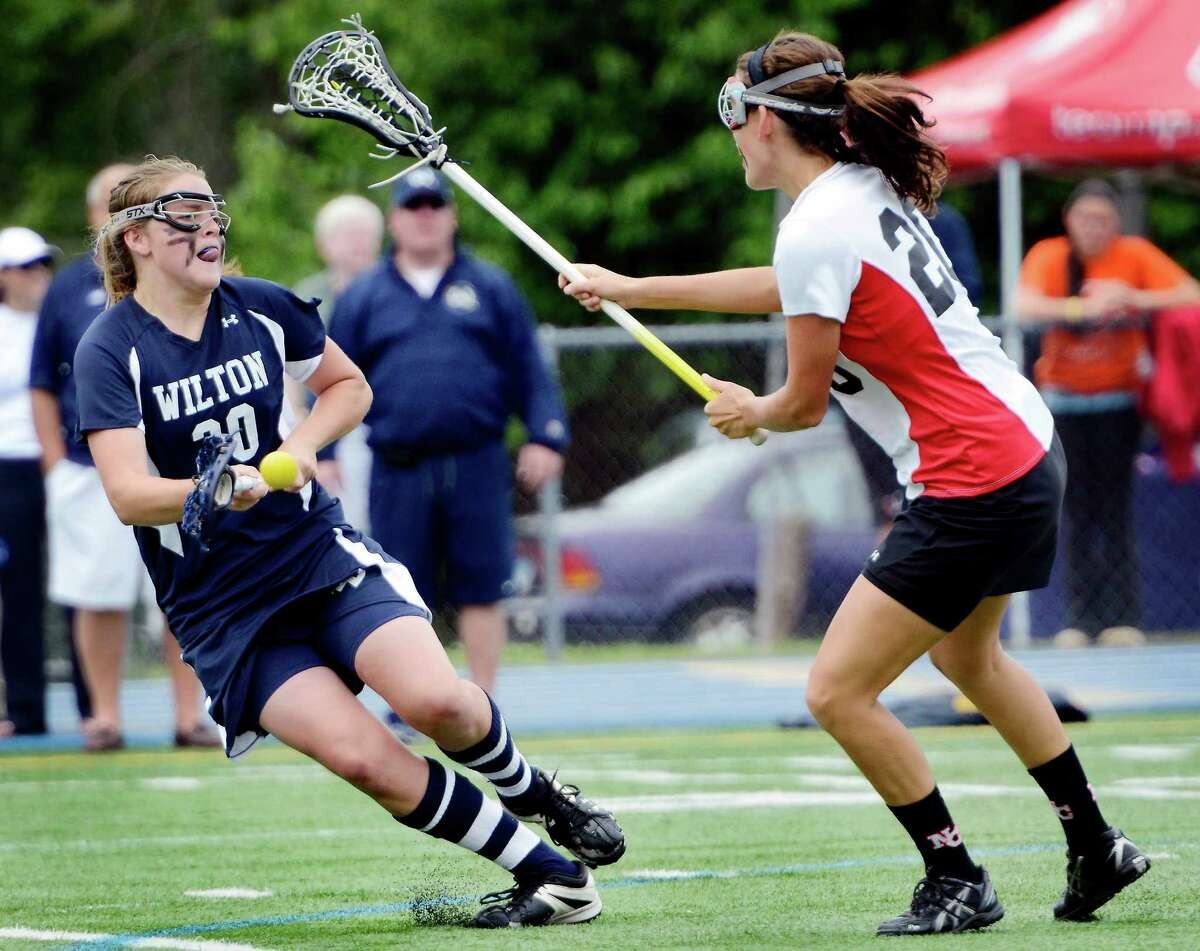 Wilton High School's Megan Boepple, covered by New Canaan High School's Julia Tuttle, takes a shot on goal during the CIAC Class M girls lacrosse championship held at Bunnell High School, Stratford, CT on Saturday June 9th, 2012.