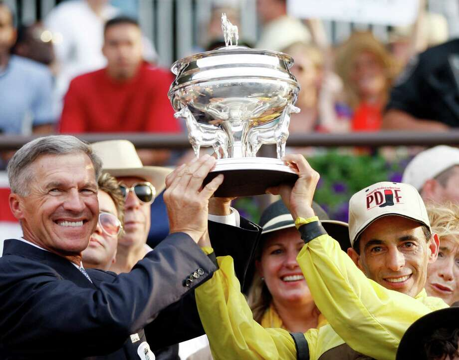 Trainer Michael Matz, left, and jockey John Velazquez hoist the trophy after Velazquez rode Union Rags to the win in the Belmont Stakes horse race at Belmont Park in Elmont, N.Y., on Saturday, June 9, 2012. (AP Photo/Mike Groll) Photo: Mike Groll, Associated Press / AP