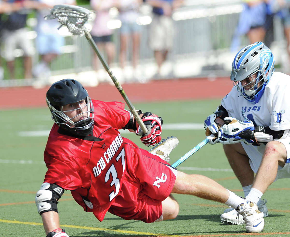 At left, Eric Persky # 37 of New Canaan gets knocked to the ground during the Class M Boys Lacrosse championship game between Darien High School and New Canaan High School at Brien McMahon Hgh School in Norwalk, Saturday, June 9, 2012. Darien won the championship 11-5.