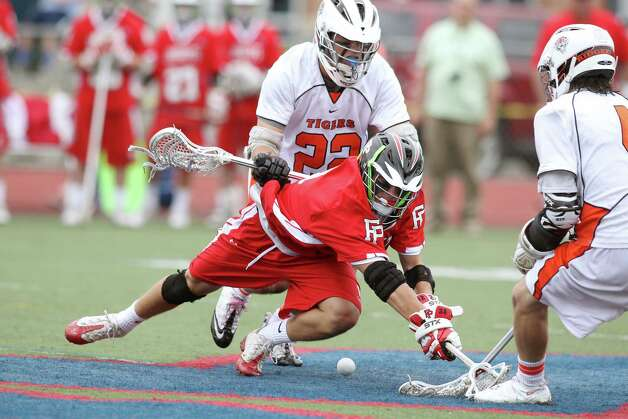Fairfield Prep middie Troy Foreit battles for control of a faceoff ball against Ridgefield's William Bonaparte and Sean Wilkinsin. Prep won the Class L CIAC acrosse final at Brien McMahon High School in Norwalk, conn. on Saturday June 9, 2012., 8-6. Photo: J. Gregory Raymond / Connecticut Post Freelance