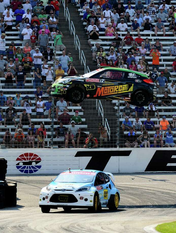 Stephan Verdier goes airborne as Marcus Gronholm, drivse beneath in the Global Rallycross Championship at Texas Motor Speedway. Photo: AP