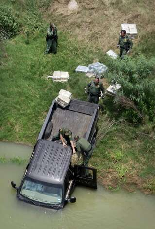 Border agents remove packages of drugs from a stolen pickup truck that had been detected and chased back to the Rio Grande River where the occupants ditched the truck in the river and swam back to Mexico.  Thursday, May 3, 2012. Photo: Bob Owen, San Antonio Express-News / © 2012 San Antonio Express-News