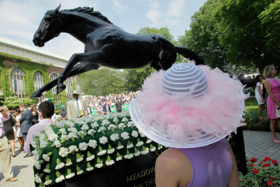 Julia Hanson, 8, of Chicago, looks at a statue of 1973 Triple Crown winner Secretariat prior to the Belmont Stakes horse race, Saturday, June 9, 2012, at Belmont Park in Elmont, N.Y. I'll Have Another, who won both the Kentucky Derby and the Preakness, was scratched Friday from the Belmont Stakes, ending his shot at the Triple Crown. Photo: Mark Lennihan, Associated Press / AP
