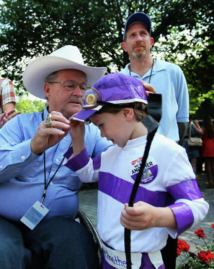 Ron Turcotte, jockey of 1973 triple crown winner Secretariat, jokes with five-year-old Kenny Foudy of Port St. Lucie, Fla. in the paddock before the start of the 144th Belmont Stakes at Belmont Park on June 9, 2012 in Elmont, New York. Photo: Rob Carr, Getty Images / 2012 Getty Images
