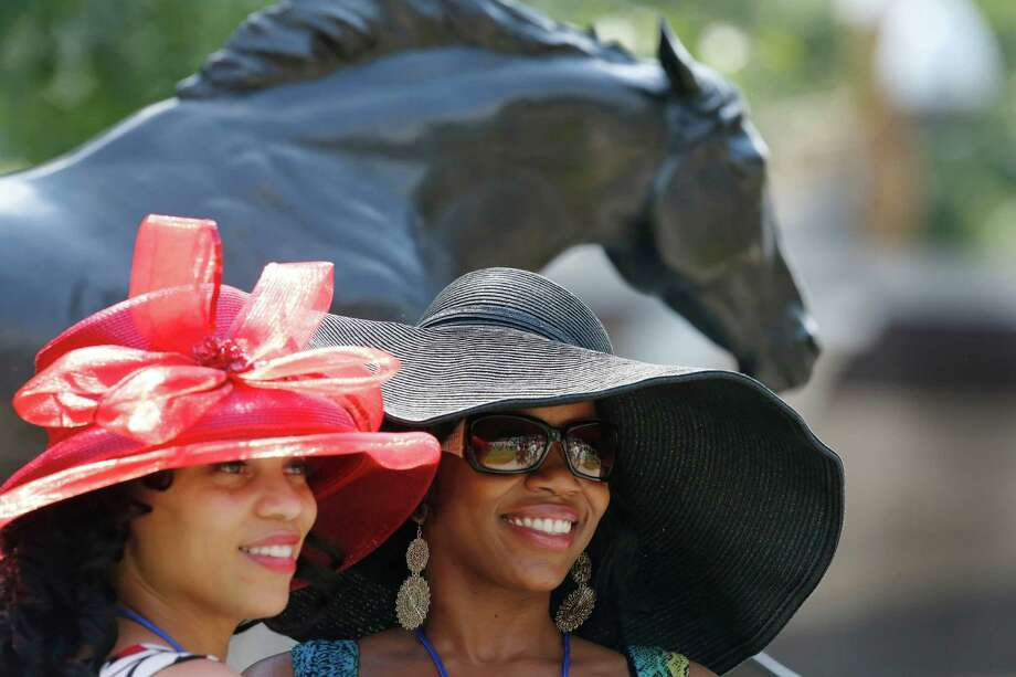 Jami Jordan, left, of Carlisle, Pa., and Tonia Cooke, of Oakdale, N.Y., pose for photos by a statue of 1973 Triple Crown winner Secretariat prior to the Belmont Stakes horse race, Saturday, June 9, 2012, at Belmont Park in Elmont, N.Y. I'll Have Another, who won both the Kentucky Derby and the Preakness, was scratched Friday from the Belmont Stakes, ending his shot at the Triple Crown. Photo: Mark Lennihan, Associated Press / AP