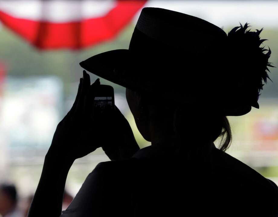 Eva Kitova of New York takes photos before the horse racing day starts at Belmont Park in Elmont, N.Y., on Saturday, June 9, 2012. The 144th Belmont Stakes horse race will be run later today. Photo: Mike Groll, Associated Press / AP