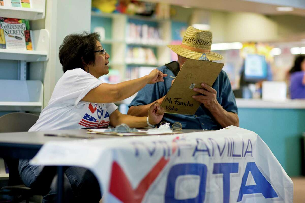 Linda Vargas, a volunteer with Mi Familia Vota, a national group that helps Latinos become citizens and register to vote, assists Harvey Stroh with registration papers last month in Denver.
