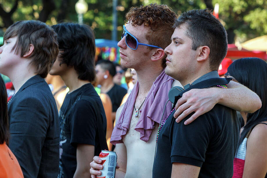 Two men in the audience listen intently to the keynote speecch by transgender activist Nikki Araguz during PrideFest at HemisFair Park on June 9, 2012. Photo: Marvin Pfeiffer/ Express-News