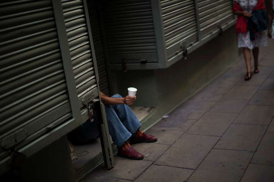 A man begs in a street in Barcelona, Spain, on Saturday. Spain requested a bank bailout from the eurozone, becoming the largest country to seek help since the single currency bloc's debt crisis erupted. Photo: Emilio Morenatti / AP