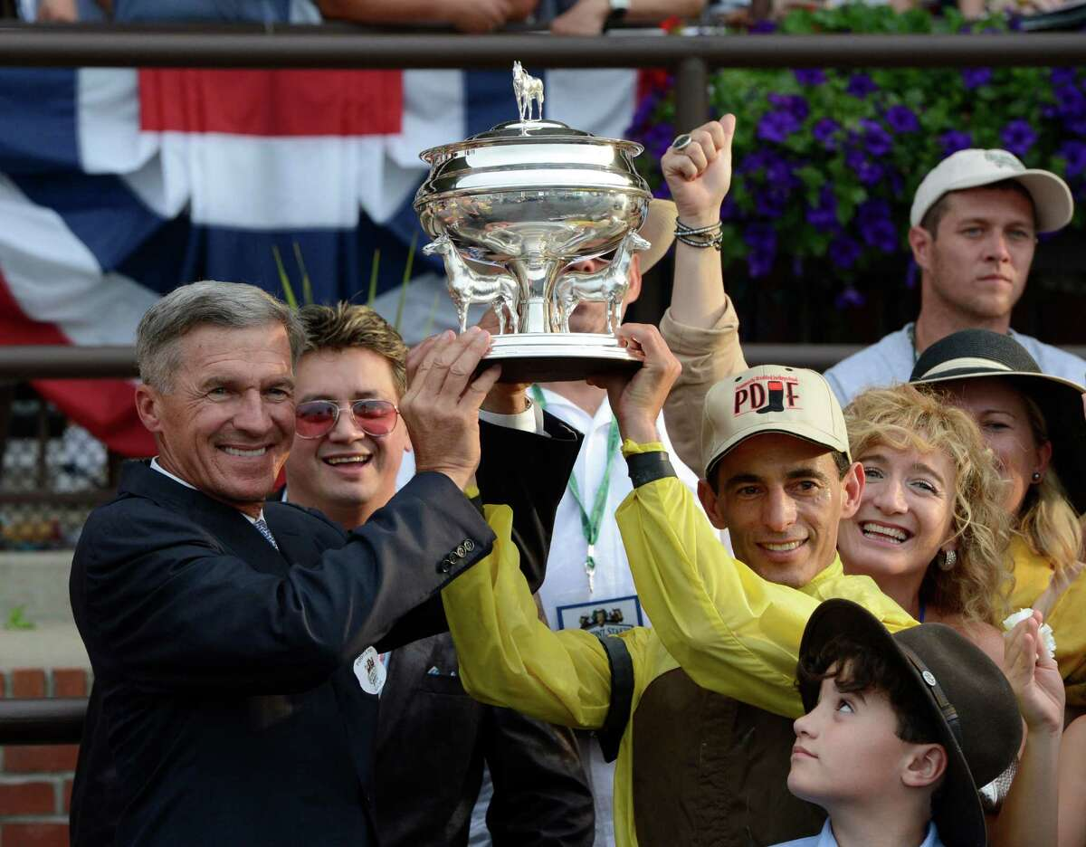 Trainer Michael Matz,left and jockey John Velazquez John Velazquez hold the winner's aloft after Union Rags won the 144th running of the Belmont Stakes at Belmont Park in Elmont, N.Y. June 9, 2012. (Skip Dickstein / Times Union)