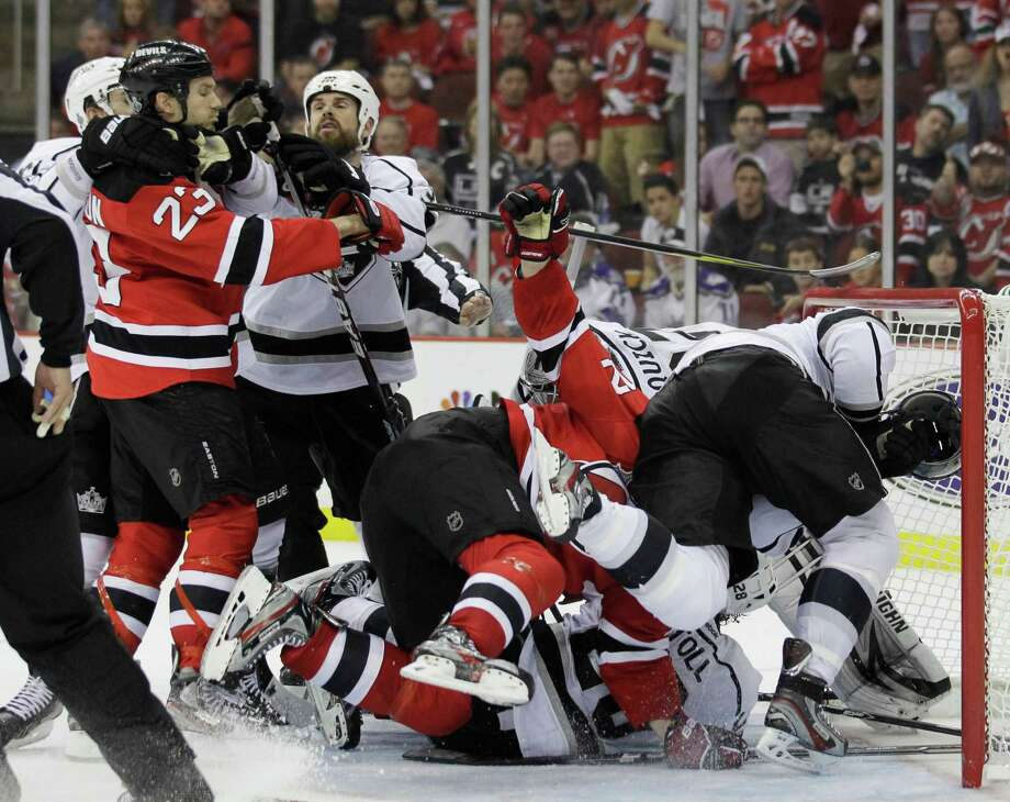 New Jersey Devils and Los Angeles Kings players grapple near the goal in the third period during Game 5 of the NHL hockey Stanley Cup finals, Saturday, June 9, 2012, in Newark, N.J.. (AP Photo/Julio Cortez) Photo: Julio Cortez, Associated Press / AP
