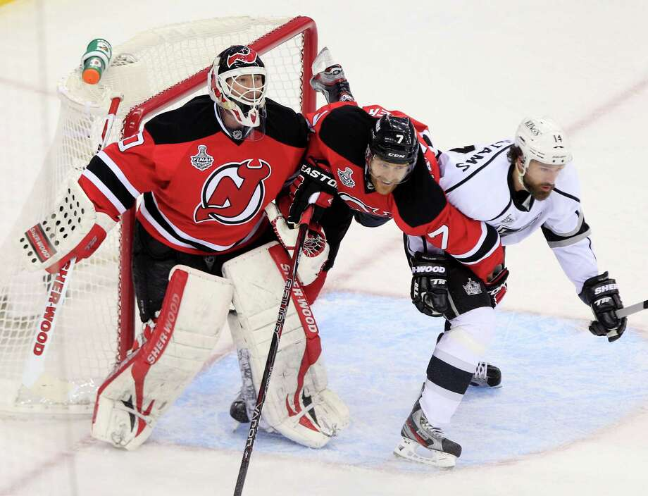 New Jersey Devils' Henrik Tallinder, center, struggles with Los Angeles Kings' Justin Williams near goalie Martin Brodeur in the second period during Game 5 of the NHL hockey Stanley Cup finals, Saturday, June 9, 2012, in Newark, N.J.. (AP Photo/Frank Franklin II) Photo: Frank Franklin II, Associated Press / AP
