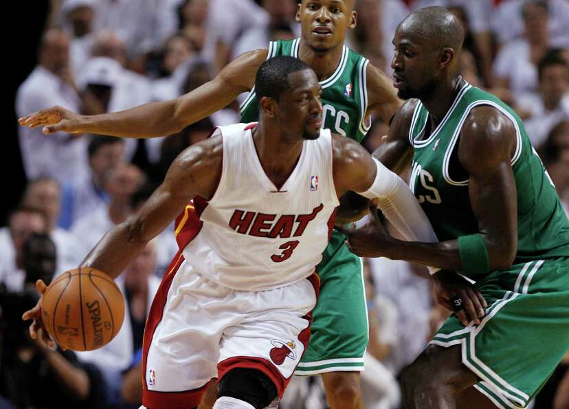 Miami Heat's Dwyane Wade (3) dribbles as Boston Celtics' Kevin Garnett, right, defends during the se
