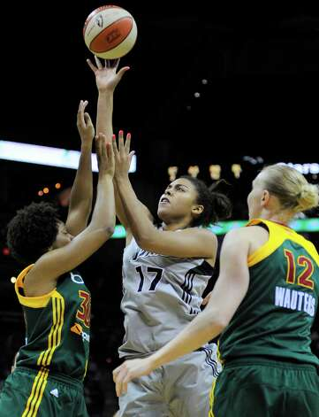 San Antonio Silver Stars' Ziomara Morrison, center, of Chile, shoots between Seattle Storm's Tanisha Wright, left, and Ann Wauters, of Belgium, during the first half of a WNBA basketball game, Saturday, June 9, 2012, in San Antonio. Photo: Darren Abate, Express-News
