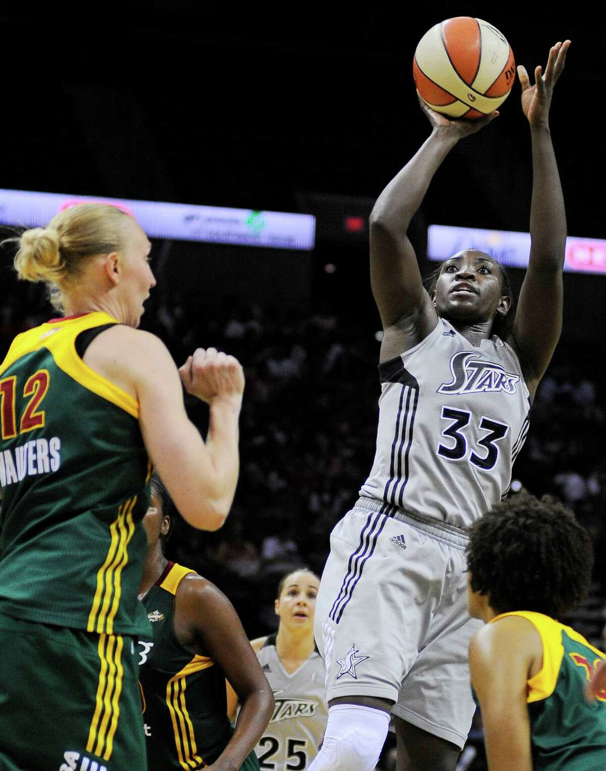 San Antonio Silver Stars' Sophia Young (33) shoots between Seattle Storm's Ann Wauters (12), of Belgium, and Tanisha Wright during the second half of a WNBA basketball game, Saturday, June 9, 2012, in San Antonio. San Antonio won 80-67.