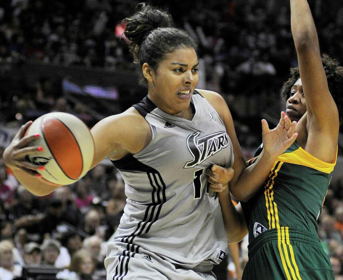 San Antonio Silver Stars' Ziomara Morrison, left, of Chile, passes around Seattle Storm's Tanisha Wright during the second half of a WNBA basketball game, Saturday, June 9, 2012, in San Antonio. San Antonio won 80-67.