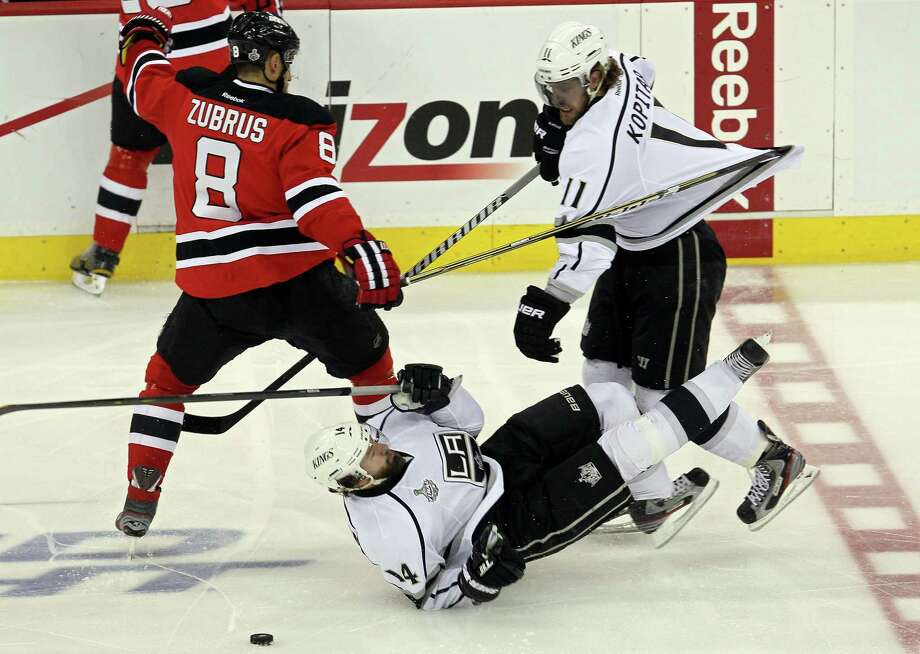 The Devils' Dainius Zubrus, left, stretches Anze Kopitar's jersey with his stick as he fights for puck possession with Kopitar and Justin Williams of the Kings. Photo: Jim McIsaac / 2012 Getty Images