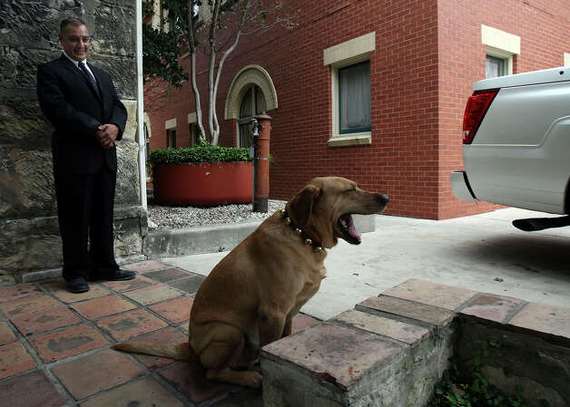 Fairmount Hotel concierge George Ortiz watches over Luke the dog on Thursday December 7, 2006. Photo: JOHN DAVENPORT, SAN ANTONIO EXPRESS-NEWS / SAN ANTONIO EXPRESS-NEWS