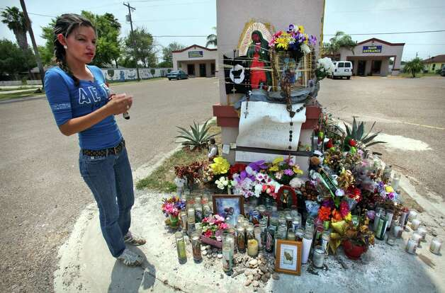 Wendy Gutierrez looks at a shrine in front of her child care center, where nine immigrants were killed, and six others injured, in a van crash, April 11, 2012 in Palmview, TX.  Border Patrol agents had attempted to stop the van a couple blocks away from the site.  Thursday, May 3, 2012. Photo: Bob Owen, San Antonio Express-News / © 2012 San Antonio Express-News