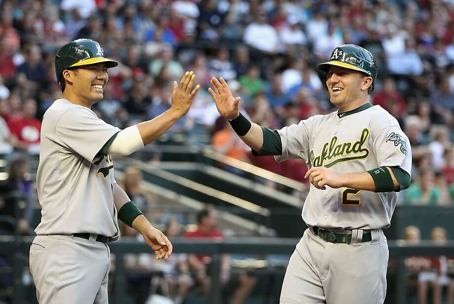 PHOENIX, AZ - JUNE 08:  Cliff Pennington #2 of the Oakland Athletics high fives Kurt Suzuki #8 after scoring against the Arizona Diamondbacks during the second inning of the interleague MLB game at Chase Field on June 8, 2012 in Phoenix, Arizona.  (Photo by Christian Petersen/Getty Images) Photo: Christian Petersen, Getty Images