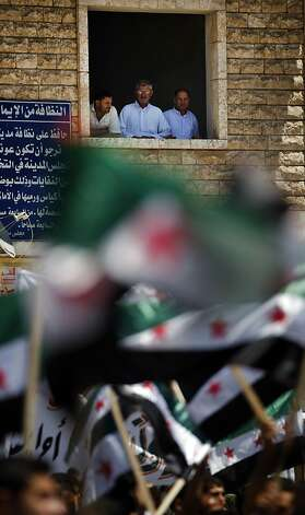 Syrian men look from a window at an anti-Bashar Assad protest after Friday prayers on the outskirts of Idlib, Syria, Friday, June 8, 2012.  (AP Photo) Photo: Anonymous, Associated Press